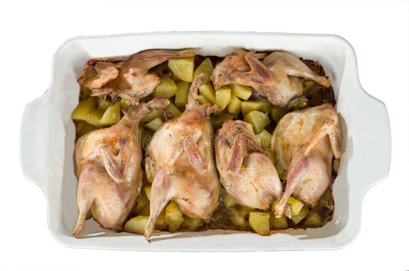 Reses muertas de las codornices con las patatas en un plato que cuece cocinado en el horno fotos de archivo libres de regalías