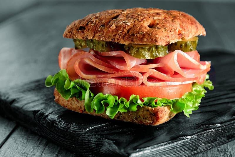 Resh三明治用火腿、乳酪、烟肉、蕃茄、沙拉、黄瓜和葱在一个木切板 库存照片