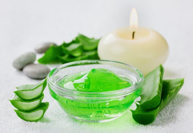 Resh-Aloevera-Blatt und -aloe gelatieren mit brennenden Kerzen auf weißer Oberfläche lizenzfreies stockbild