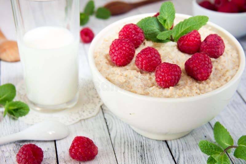 Resh heerlijk havermeel met frambozen, naast een mok met melk stock foto