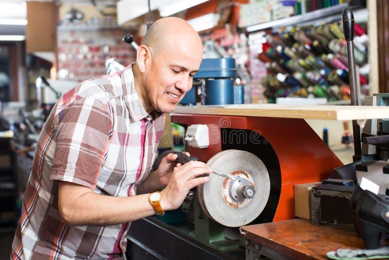 Resharpening Messer des Arbeiters auf Maschine stockbild