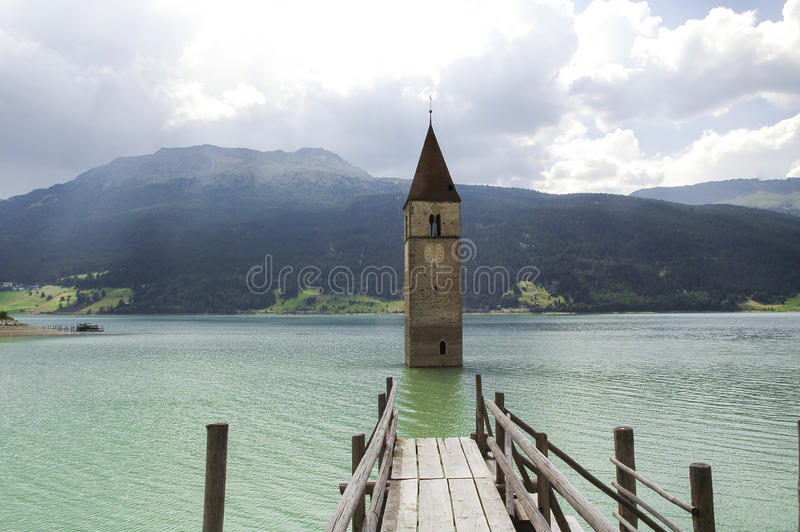 Resia, tower in the lake. Resia (Bolzano, Trentino Alto-Adige, Italy): the famous tower in the lake and wooden pier stock photo