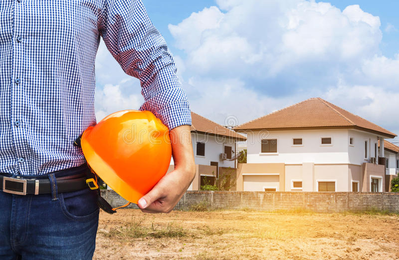 Resident engineer holding yellow safety helmet at new home building stock photography