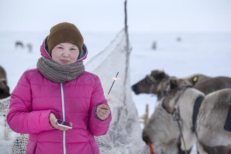 A resident of the tundra, indigenous residents of the Far North, Girl holding a sparkler, Little girl in red clothes, The girl. Holds a sparkler for the first royalty free stock images