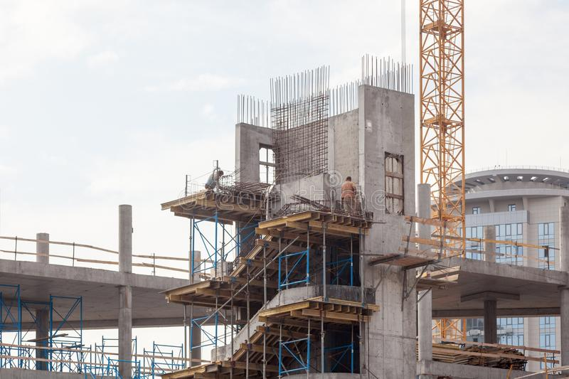 Residental building under construction. Precast concrete stairs installed. Walls made of aerated concrete blocks. Crane and new mu royalty free stock photos