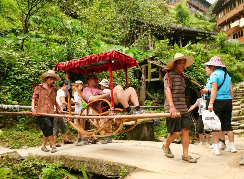Residentes del pueblo de Dazhay tomar al turista encima de la montaña para reducir drásticamente en terrazas del arroz fotografía de archivo libre de regalías