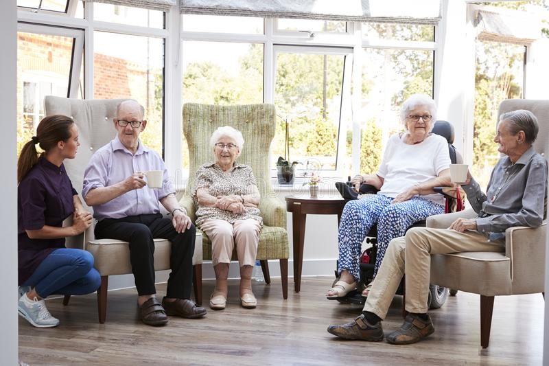 Residenti maschii e femminili che si siedono nelle sedie e che parlano con il personale sanitario in salotto della casa di riposo immagine stock