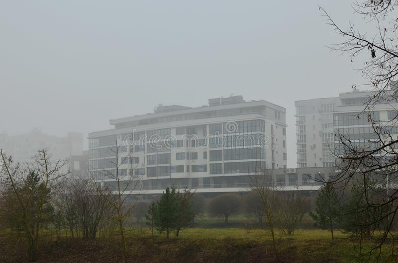 Residential apartment building on the background of the autumn landscape in a thick fog in the city. stock photos