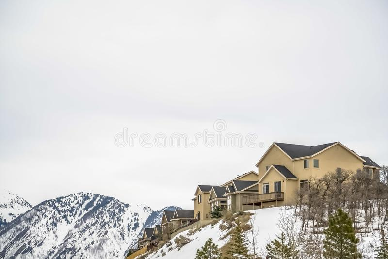Residential area on a snowy hill with conifers and leafless trees in winter. A scenic view of majestic mountain and bright cloudy sky can be seen in the royalty free stock photography