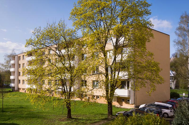 Residential block of flats apartament house building. Back side of a residential block of flats apartament house building in a tonw or city, spring trees and stock photography