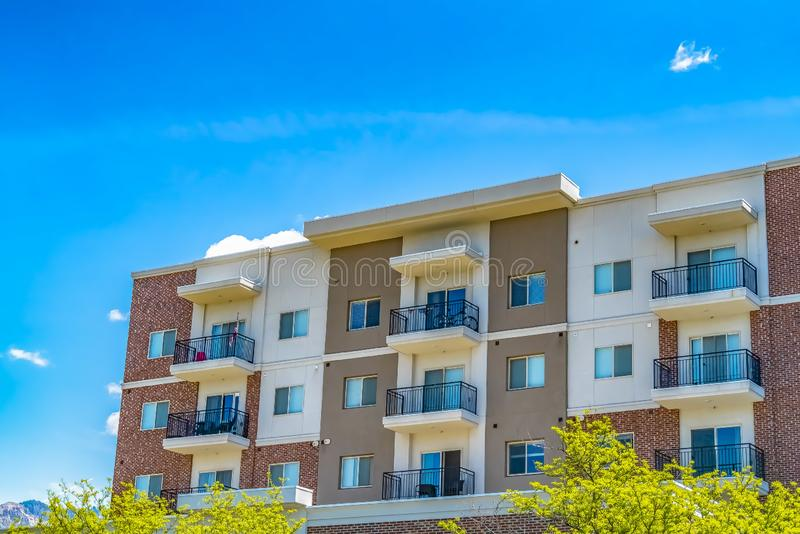 Residential building featuring red brick exterior wall and small balconies stock photos