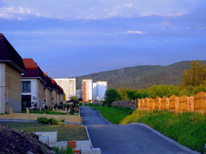 Residential buildings along the road in the light of the evening rays of the sun against a hole and a cloudy sky. Far away mountains and cloudy sky royalty free stock photography