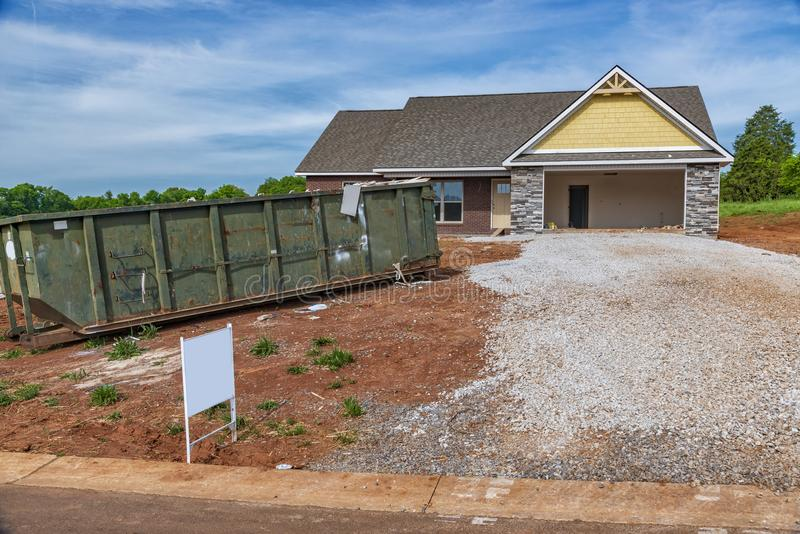 Residential Construction Site With Trash Dumpster. A residential construction site with a trash dumpster next to the driveway stock photo