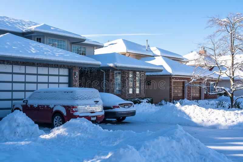 Residential driveway and front yard in snow on winter season. Residential driveway and front yard of houses in snow on winter season stock image