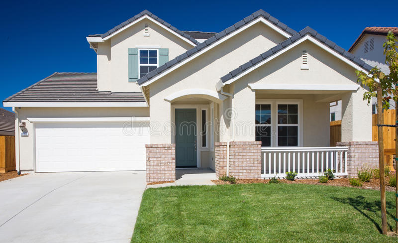 Residential Home Exterior. Front elevation of residential home. Green grass / lawn. Blue sky. New home. For sale. Stucco exterior. Front door. Driveway. Garage stock photography