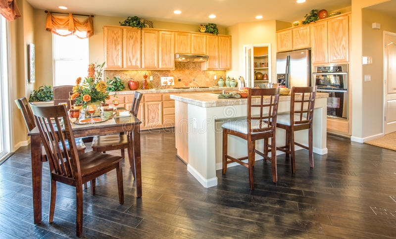 Residential Home Kitchen and Nook. Residential home kitchen and dining nook. Wood floors. Tile island and counters. Wood bar chairs. Wood nook table and chairs stock photos