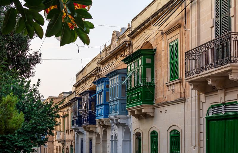 Residential house facade with traditional Maltese wooden balconies in Sliema, Malta. Coloured in orange with evening sunlight. Authentic Maltese urban scene royalty free stock image