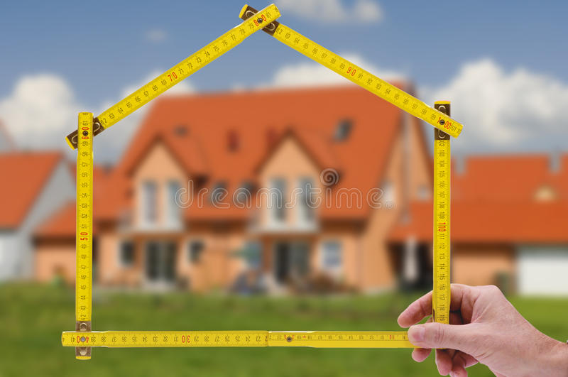 Residential house for sale. Residential house shown through an folding rule of an real estate agent royalty free stock photography