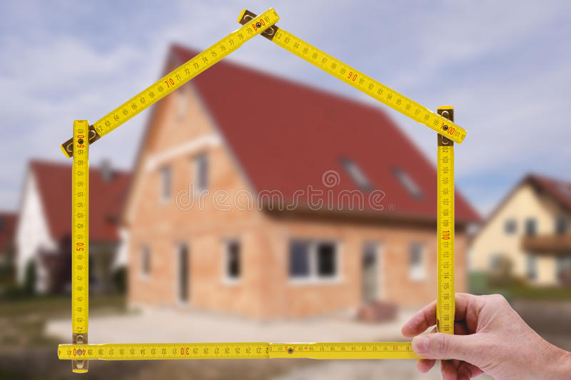 Residential house for sale. Residential house shown through an folding rule of an real estate agent royalty free stock images