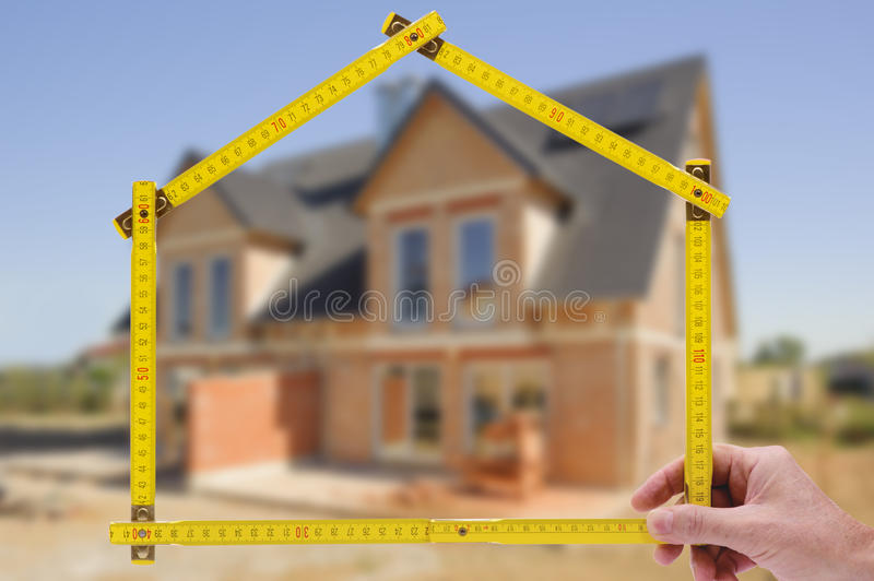 Residential house for sale. Residential house shown through an folding rule of an real estate agent stock images