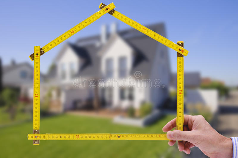 Residential house for sale. Residential house shown through an folding rule of an real estate agent stock photo