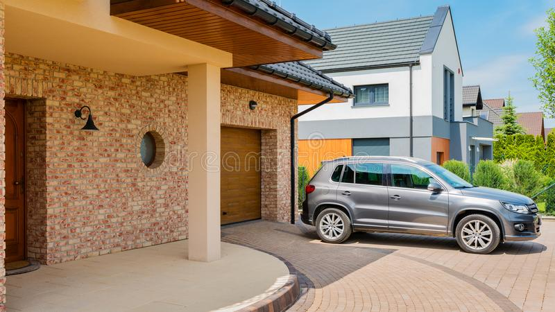 Residential house with silver suv car parked on driveway in front royalty free stock images
