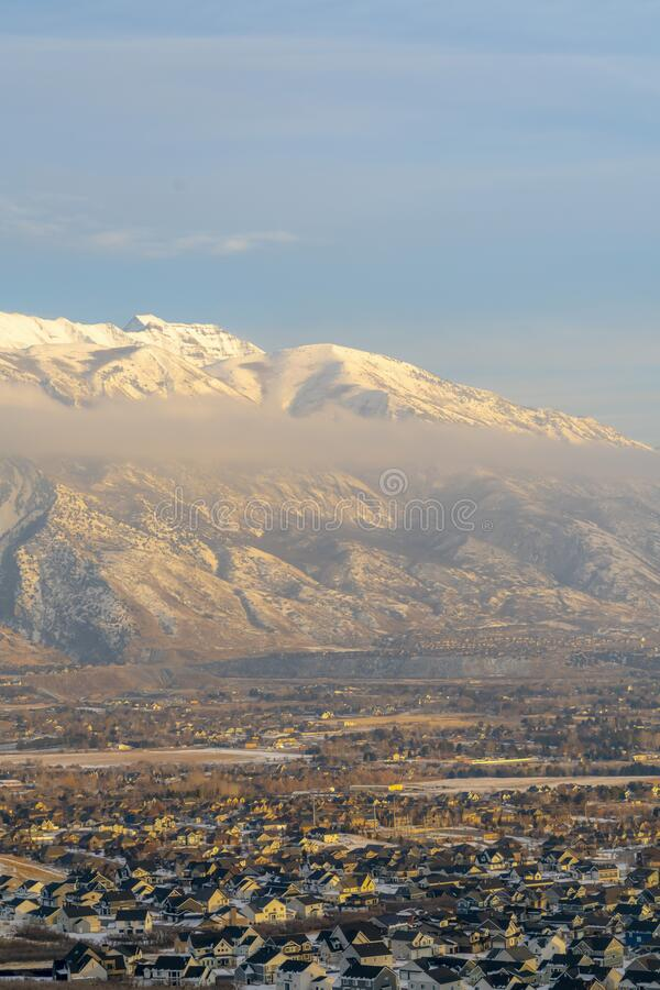 Residential houses with amazing scenic view of snowy Mount Timpanogos in winter. The snow covered peak of the towering mountain rises above gray clouds stock photos