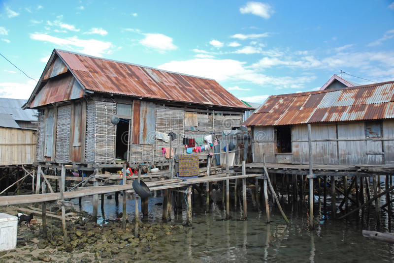 Residential houses on stilts, Maumere, Indonesia. Residential houses on stilts of bamboo/wood with metal golf roofs and drying was, Maumere, Flores, Lesser Sunda stock image
