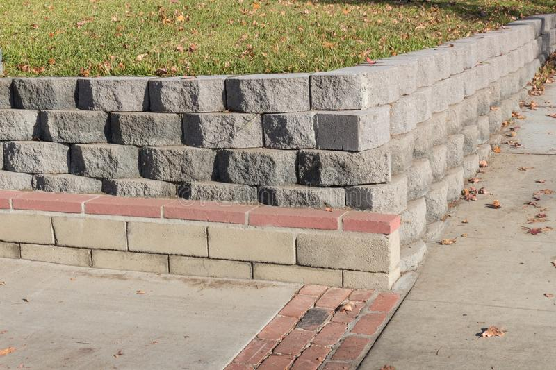 Residential retaining wall featuring a variety of stacked blocks and mortared brick textures stock image