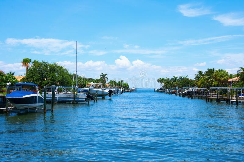 Residential saltwater canal in south Florida with blue water and many boats docks and palm trees stock photography