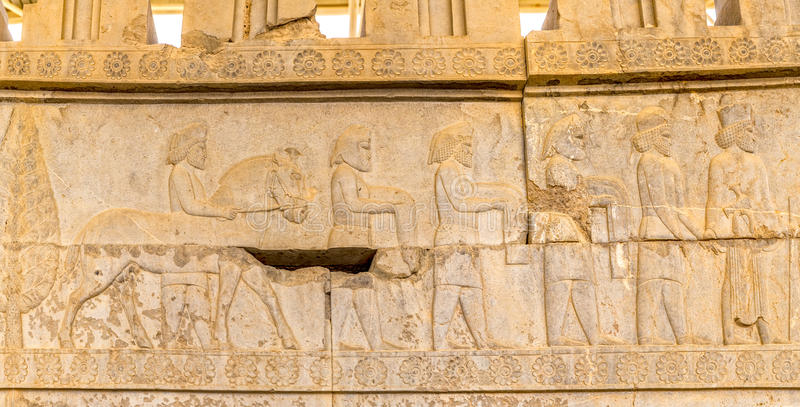 Residents of historical empire with animals in. Stone bas-relief of residents of historical empire with animals carved on the stairway facade of the Apadana at royalty free stock photography