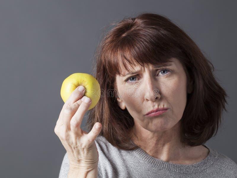 Resignerad 50-talkvinna med symbol av den sunda livsstilen och ny mat royaltyfri fotografi