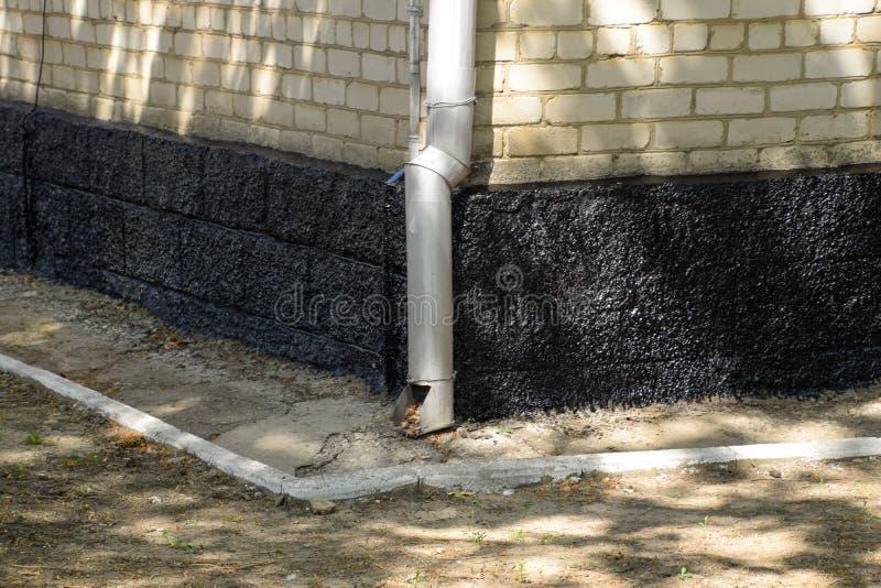 The resinized base of the house. Protection against moisture bituminous mastic. The resinized base of the house. Protection against moisture bituminous mastic royalty free stock photography
