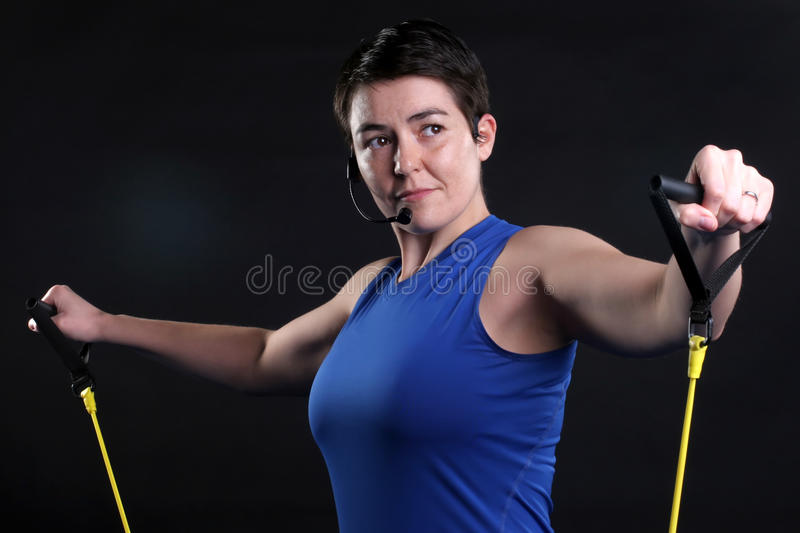 Resistance Mic. Pretty young fitness instructor with mic headset and yellow resistance bands royalty free stock image