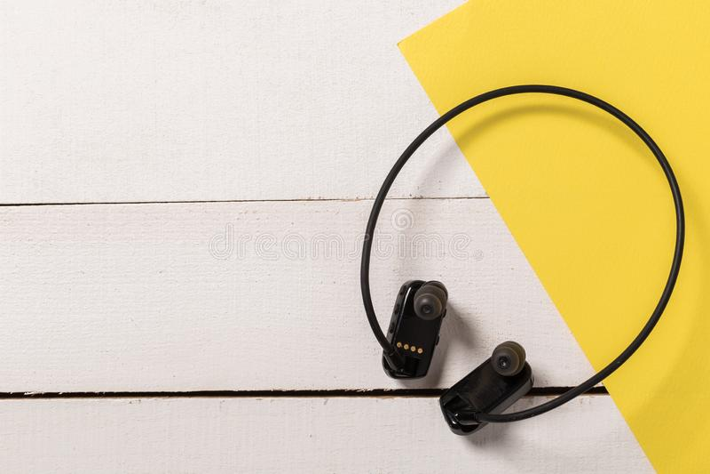 Resistent hörlurar för vatten på vit träbakgrund royaltyfri foto