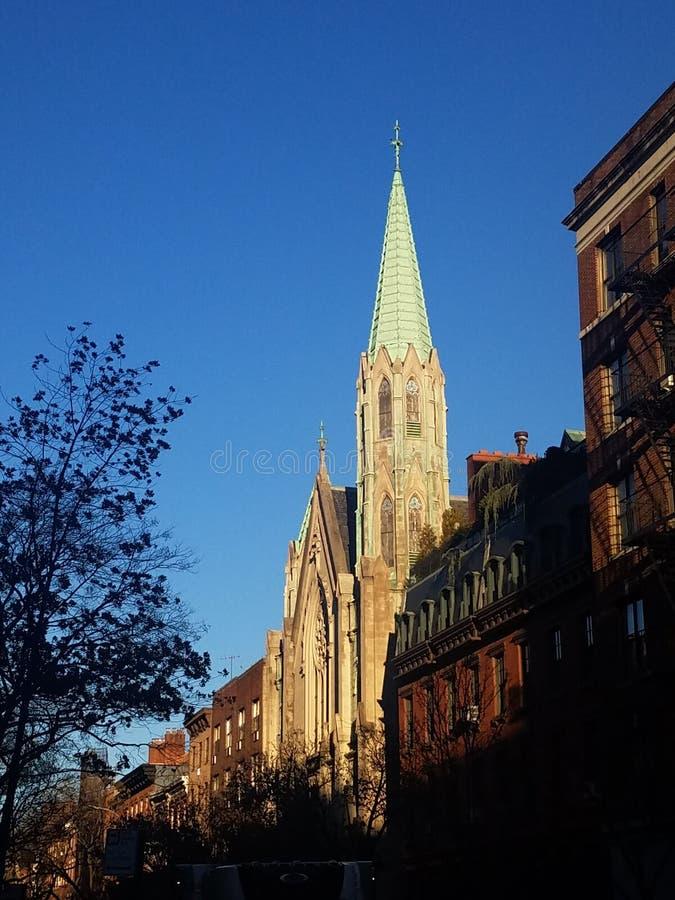 Resistindo a igreja com detalhe de cobre do pináculo e arquitetura gótico impressionante na rua histórica da vizinhança imagens de stock
