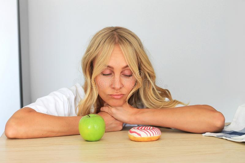 Resisting a temptation. Hesitating woman looking on donut on her table but feeling unsure about eating it or green apple royalty free stock photos