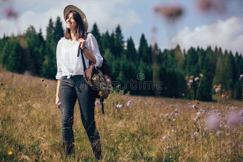 reslust- och loppbegrepp Hipsterflicka med ryggsäcken som reser i soliga berg som går i vildblommaäng stilfullt royaltyfri bild
