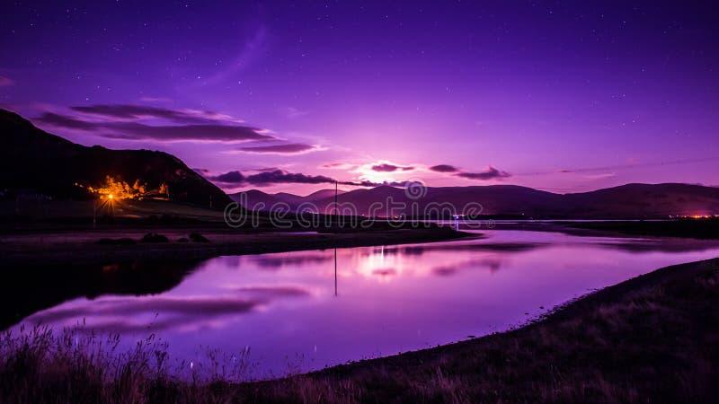 Resningmåne över vattenmånsken royaltyfri bild