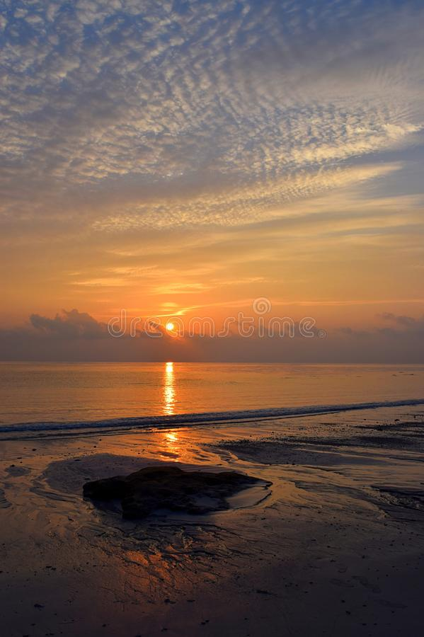 Resningsol med guld- reflexion i havsvatten med modellen av moln i himmel - Kalapathar strand, Havelock ö, Andaman royaltyfri bild