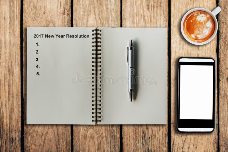 Resolución 2017 del Año Nuevo como nota en la taza del cuaderno y de café imagen de archivo