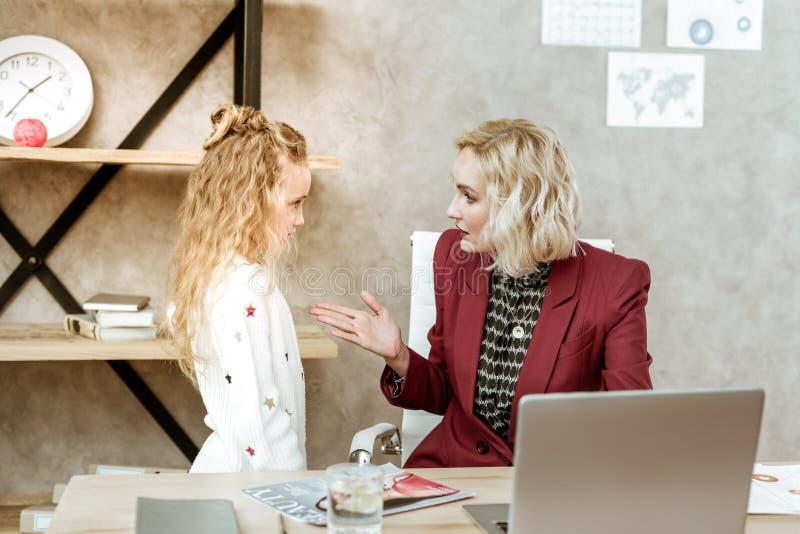 Resolute moeder in rood jasje die ernstig gesprek hebben royalty-vrije stock afbeeldingen