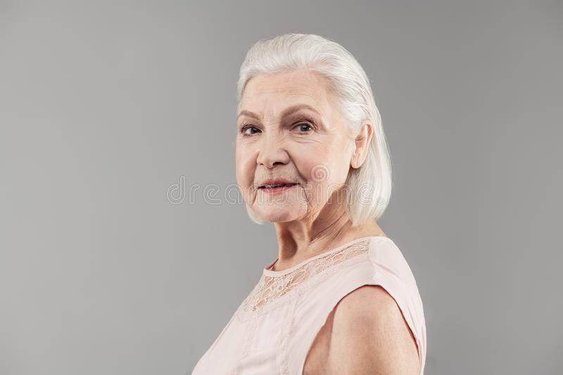 Resolute senior lady with tidy bob haircut looking aside. Professional photo studio. Resolute senior lady with tidy bob haircut looking aside while participating stock photos
