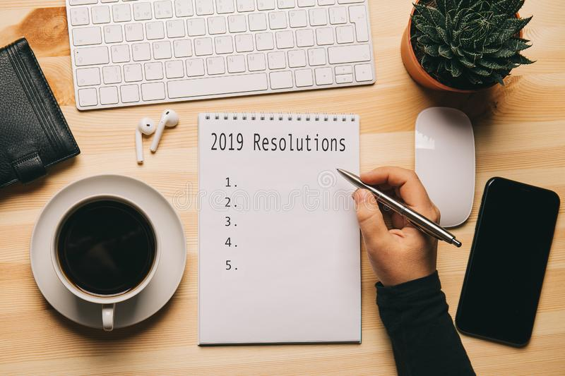 2019 Resolutions - text on notebook at work place top view, check list or plan of business strategy for motivation and inspiration. Vintage toned royalty free stock photography