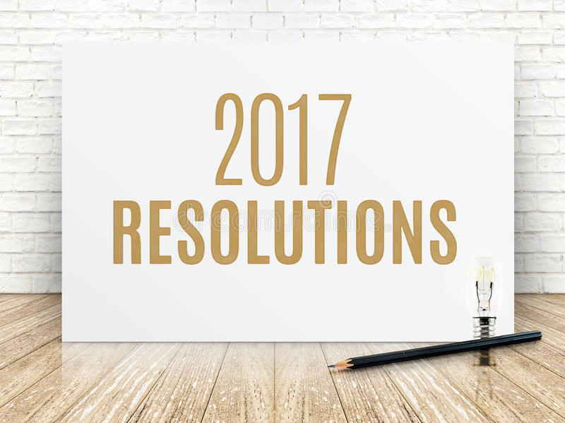2017 resolutions text on white paper poster with black pencil an. D lightbulb on wood plank floor and white brick wall stock photos