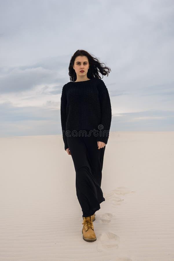 Resoluut meisje, in zwarte, gangen door de woestijn stock fotografie