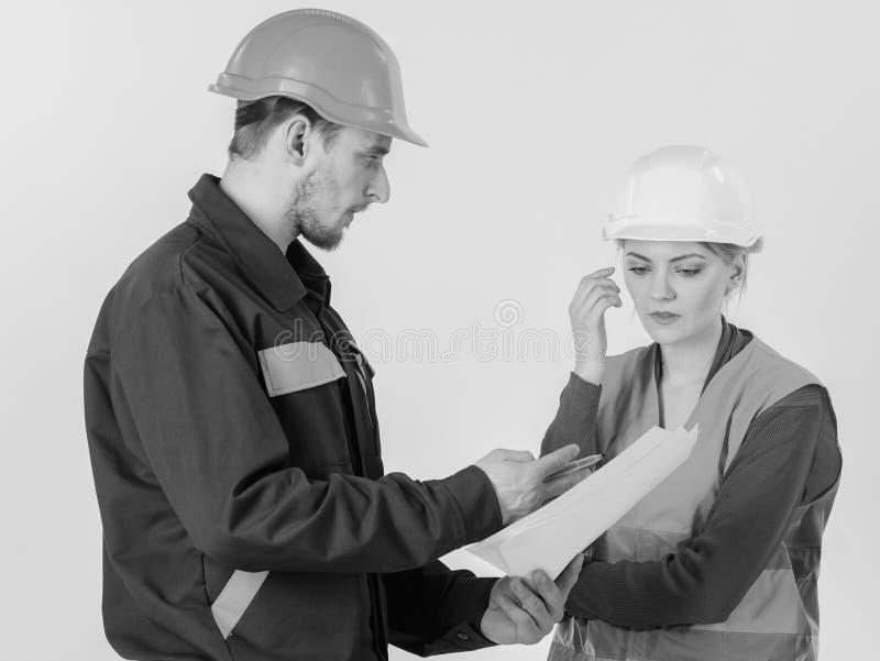 Resolvendo o conceito dos problemas O homem e a mulher nos capacetes de segurança, uniforme olham o modelo foto de stock royalty free