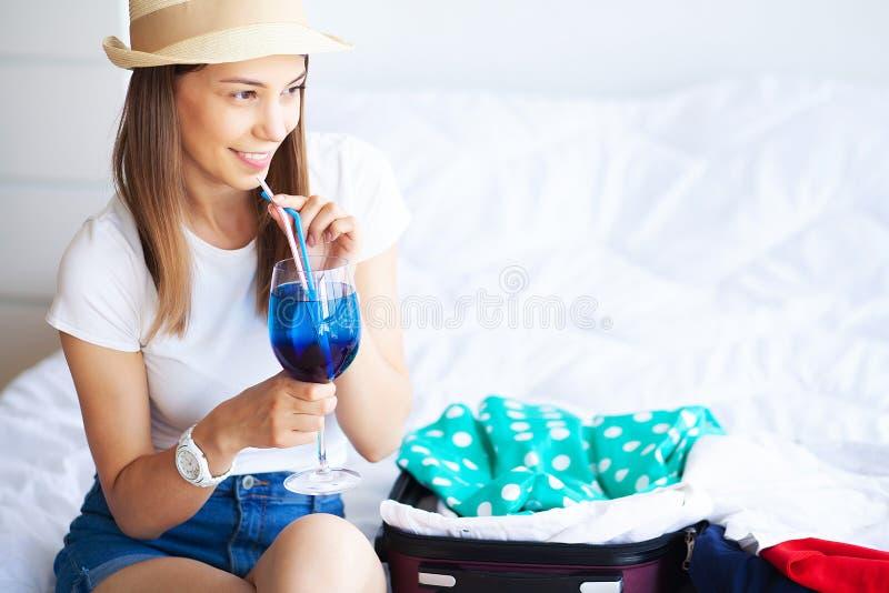 Resor Den lyckliga kvinnan packar resv?skan hemma arkivfoton