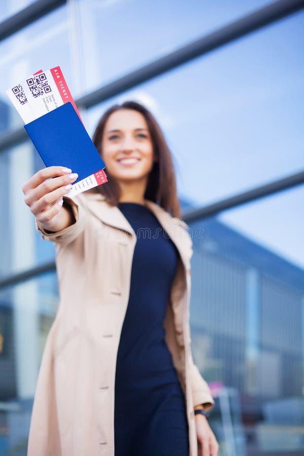 Resor Flygbiljett för kvinnainnehav två i utlandpass nära flygplats royaltyfri fotografi