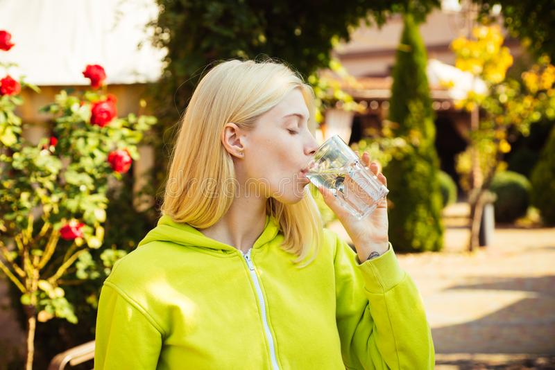 Resort with mineral water sources. Healthy lifestyle. Enjoy every sip of crystal clear water in blooming garden. Girl. Drink water. Woman enjoy mineral water stock photo
